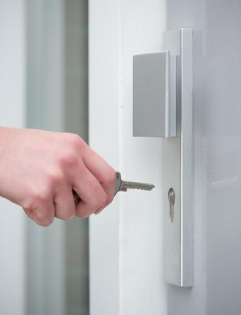 enter key: Close up female hand unlocking door lock