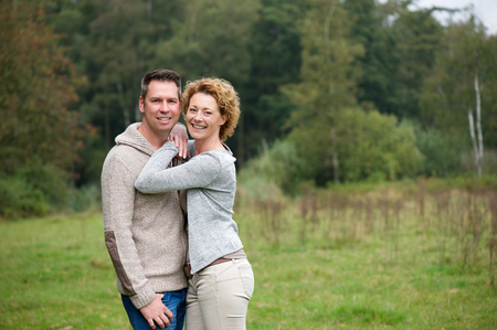 mid adult men: Portrait of a happy couple smiling and hugging outdoors