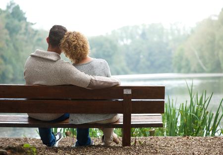 야외 벤치에 앉아 행복한 커플의 후면보기