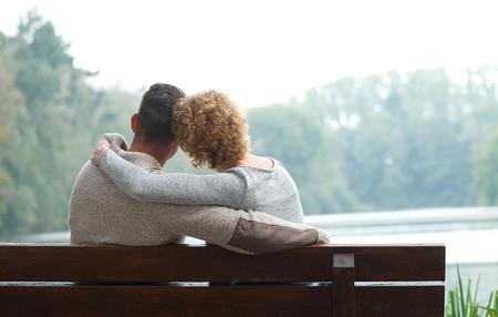 parejas romanticas: Pareja cari�osa sentados juntos en el banquillo por el lago Foto de archivo
