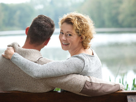 Portrait of a happy couple sitting on bench outdoors Stock Photo