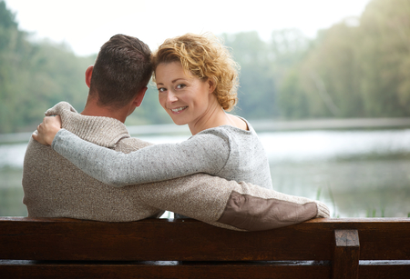 Portrait of a couple sitting on bench by a lake with woman smiling