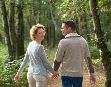 행복한 커플이 손을 잡고 숲에서 산책의 초상화