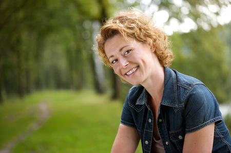 Zavřete portrét atraktivní žena s úsměvem venku v lese