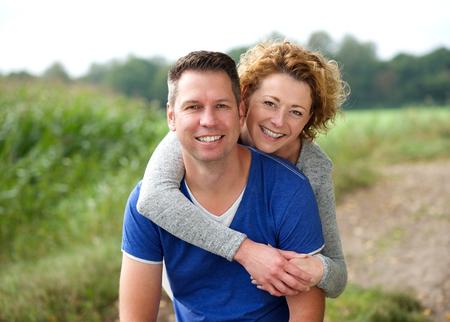 屋外彼氏を抱いて笑顔の女性の肖像画を間近します。