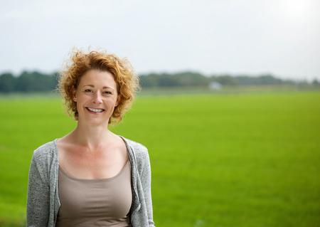 緑の田園地帯で屋外笑顔の魅力的な女性の肖像画