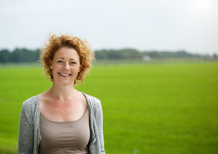 Portrait of an attractive woman smiling outdoors by green countryside