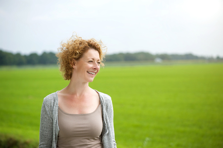 Portrait of a beautiful woman smiling outdoors by green countryside  photo