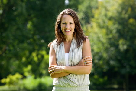 Portrait of a lady standing in nature with arms crossed Stock Photo