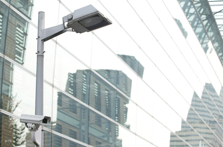 int: CCTV security camera lamp pole protecting business building int he city