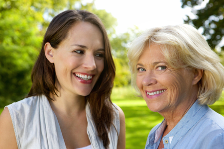 grown ups: Close up horizontal portrait of senior mother smiling with older daughter