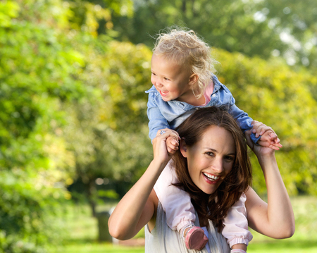 Close up portrait of a smiling mother carrying cute little girl on shoulders Stock Photo