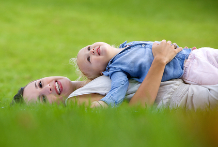 lying on side: Side view portrait of a smiling mother lying down on grass with cute baby