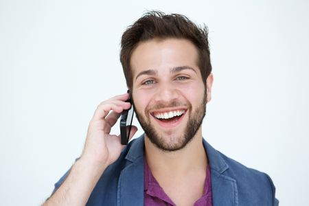 Close up portrait of a cool young man smiling with mobile phone on white background