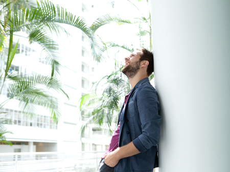 lifestyle caucasian: Profile portrait of a happy young man leaning against wall in bright building