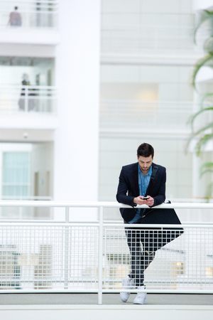 businessman waiting call: Young businessman standing in office building sending text message on mobile phone