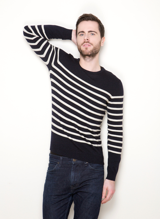 Portrait of a trendy young man posing against white background photo