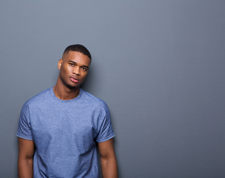beauty model: Portrait of an attractive african american man posing on gray background