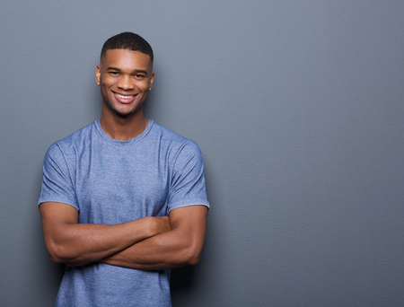 Portrait of a smiling black man posing with arms crossed on gray background