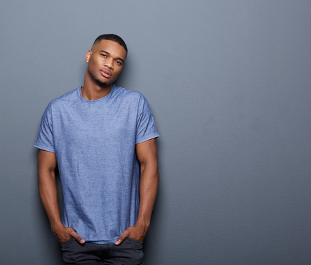 Portrait of a cool african american guy posing on gray background