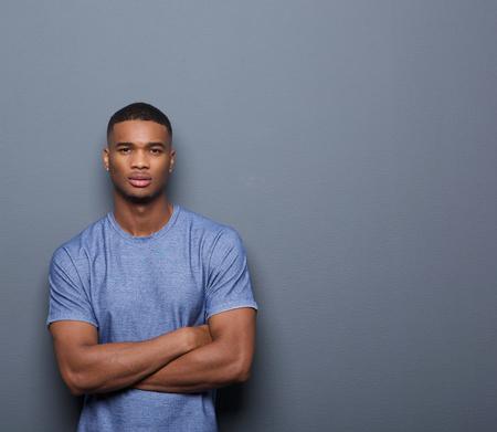 Portret van een knappe Afro-Amerikaanse man die met de armen gekruist op een grijze achtergrond