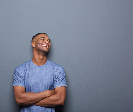 happy face: Portrait of a happy african man laughing with arms crossed on gray background Stock Photo