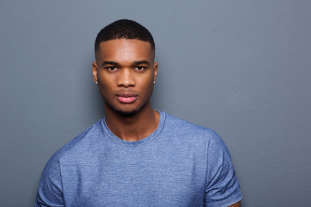 Close-up portret van een knappe jonge zwarte man met ernstige uitdrukking op het gezicht