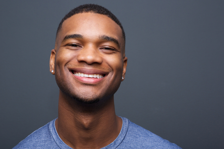 Close up portrait of a happy black man smiling on gray background Stock Photo