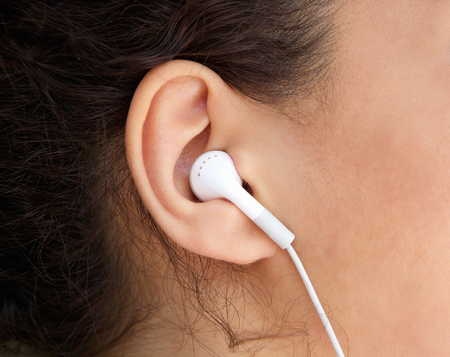 ear phones: Close up young woman ear with earphone