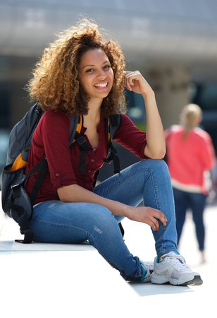 african education: Portrait of a cheerful female student sitting outside with bag Stock Photo