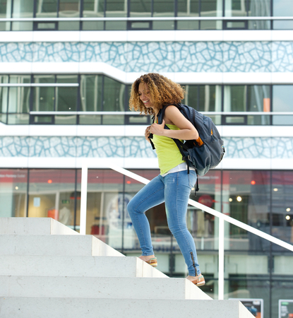 happy black woman: Portrait of a happy female student walking on campus with backpack