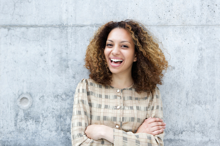 woman pose: Close up portrait of a cheerful young woman laughing outdoors with arms crossed