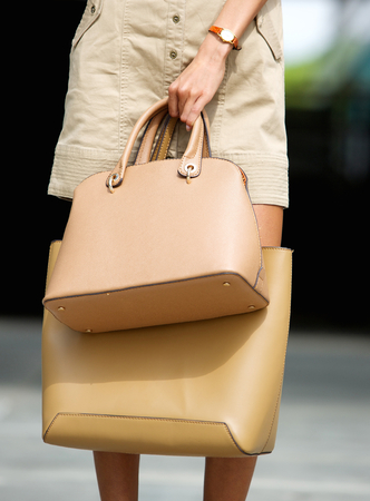 Close up fashionable young woman holding tan leather handbags outdoors photo