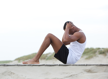 man working out: Side view portrait of a young man exercising on the beach doing sit ups
