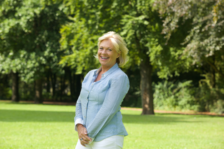 middle aged woman smiling: Portrait of a happy older woman smiling outdoors Stock Photo