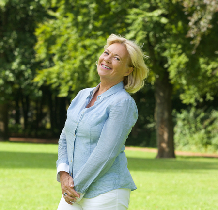 middle aged woman smiling: Portrait of a middle aged woman smiling outdoors