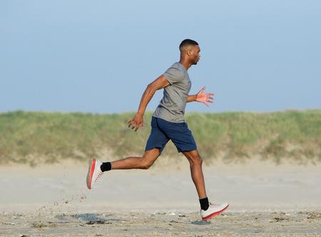 atleta corriendo: Vista lateral de un hombre afroamericano a correr por la playa