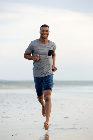 Smiling young man running barefoot at the beach photo