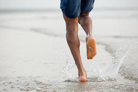 Rückansicht Untersicht eines Mannes barfuß im Wasser laufen Standard-Bild - 32266293