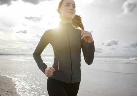 sports and fitness: Close up portrait of a woman jogging outdoors by the beach Stock Photo