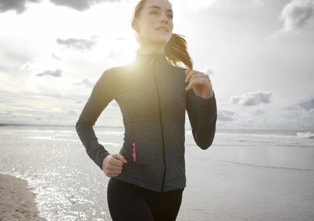 Close-up portret van een vrouw joggen buiten bij het strand