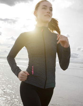 running water: Close up portrait of a woman running outdoors by the beach Stock Photo