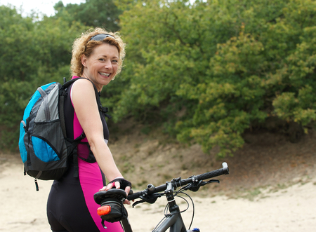 middle aged woman smiling: Portrait of a middle aged woman smiling with bike