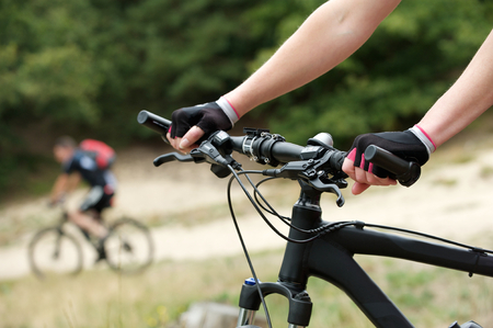 handle bars: Close up woman hands on bicycle handle bars Stock Photo