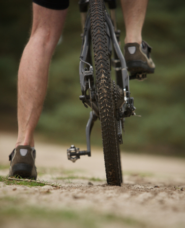 bicycle pedal: Rear view low angle man legs on mountain bike outdoors