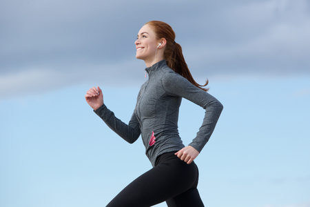 side profile: Portrait of a woman smiling and running outdoors Stock Photo