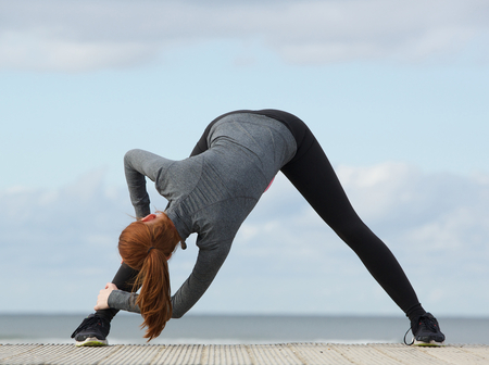 bending down: Young sporty woman bending down and stretching exercise