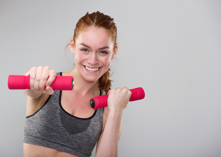 Close up portrait of a smiling sports woman holding weights photo