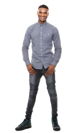 Volledige lengte portret van een koele zwarte man glimlachend op witte achtergrond