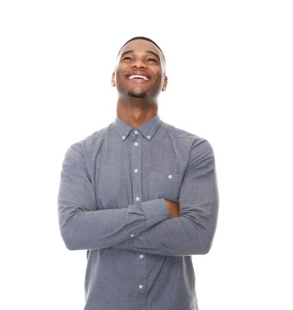 hombres de negro: Close up retrato de un hombre negro joven riendo con los brazos cruzados sobre fondo blanco aisladas Foto de archivo